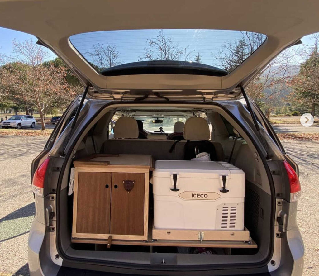 Toyota Sienna camper van with hatch raised to see kitchen area and cooler