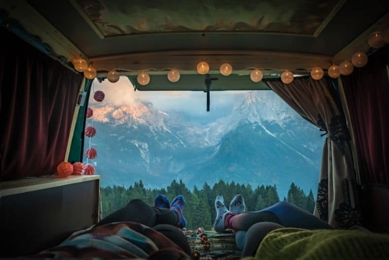Two people lie in minivan overlooking mountains