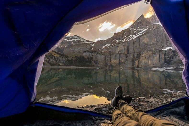 Tent opening overlooks mountains reflected in a lake