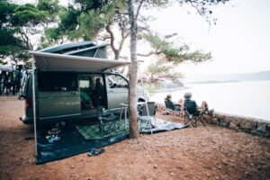 Family boondocking in a van by a lake