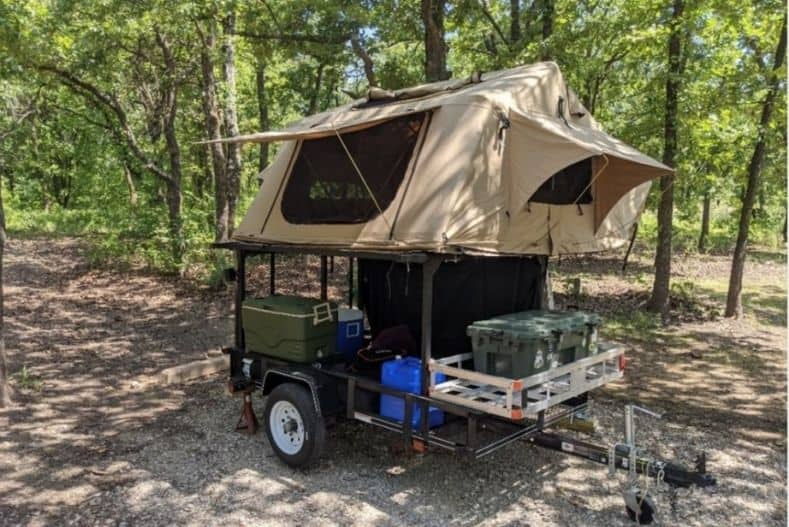 DIY Utility Trailer Camper with rooftop tent mounted to metal frame, storage underneath