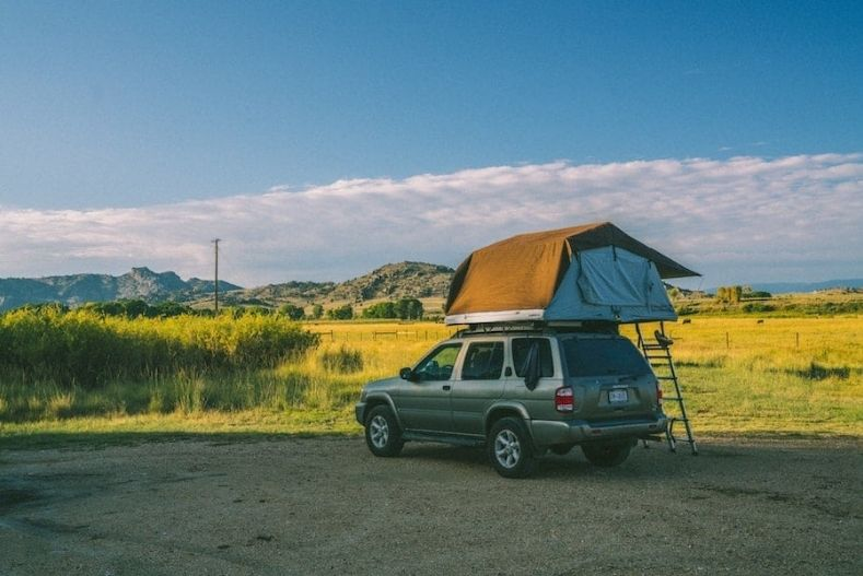 SUV with rooftop tent set up on roof
