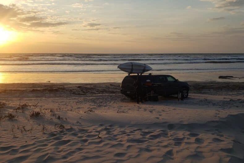 Truck camper parked on a sandy beach