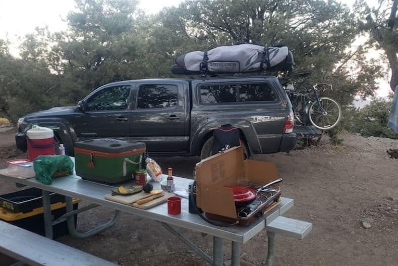 Truck camping site with picnic table, cooler, camp stove and other camping accessories