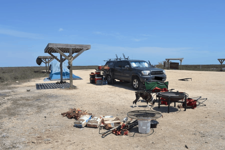 Truck camping site with tent, fire pit, fire wood and camping table around truck