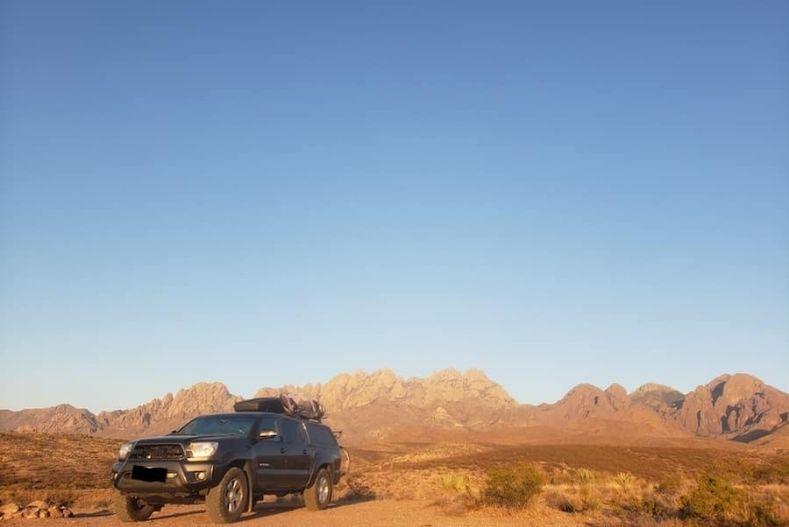 Truck camper with desert landscape and blue sky above
