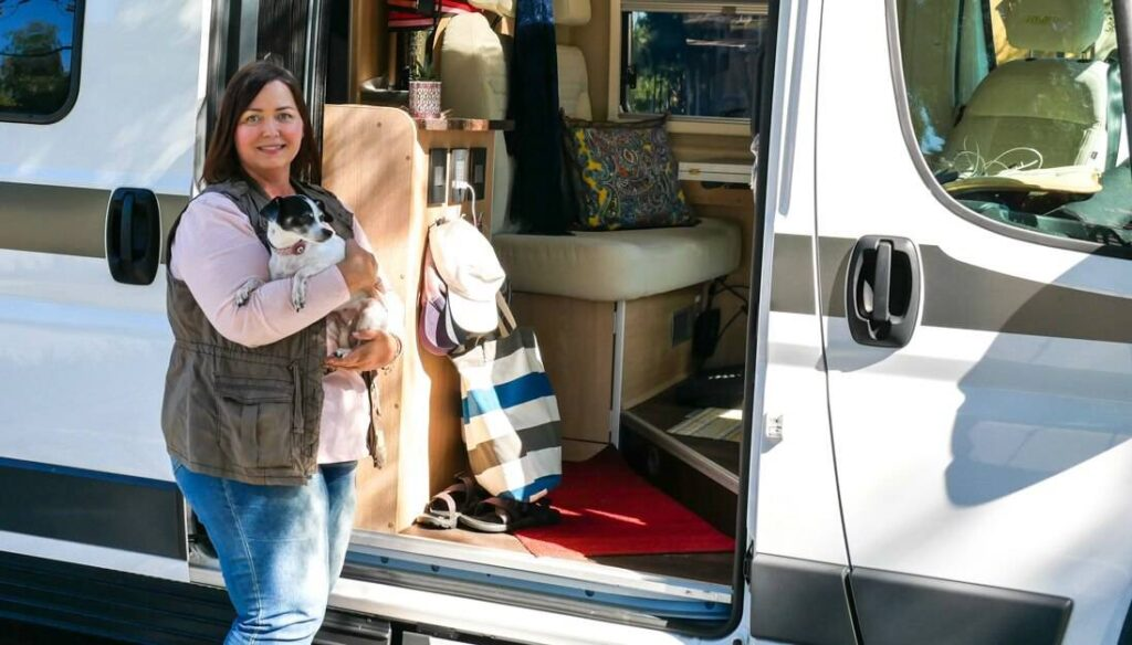 Amber Baldwin poses in front of her RV with a dog. She uses Zion as health insurance for full time RVers