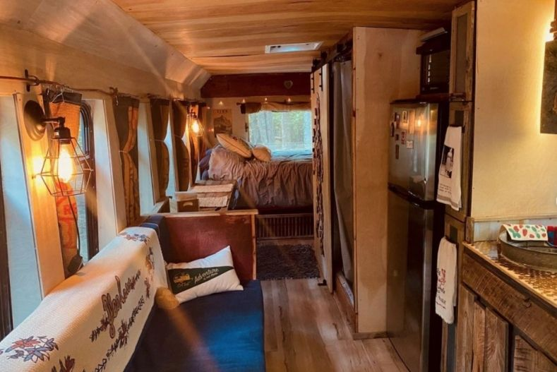 Interior of Big Blue Bertha shuttle bus conversion with bed, cabinets, fridge and couch visible