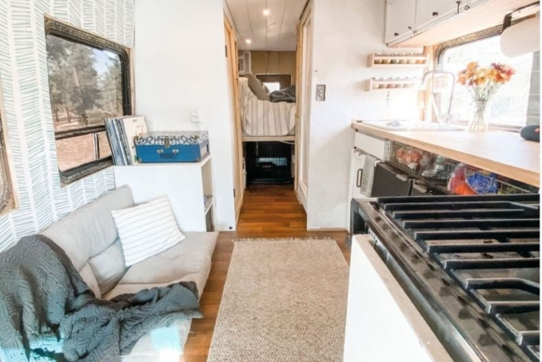 Interior of Brittany's bus conversion with stovetop, counter, sink, couch and partial view of bed