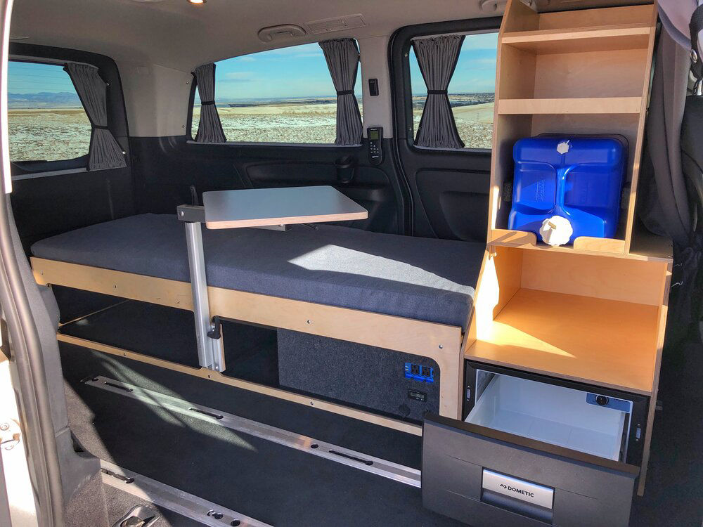 The interior of a Mercedes Metris campervan conversion with bed, table and storage