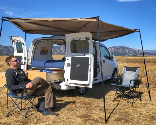 Man sitting in front of Nissan NV200 camper