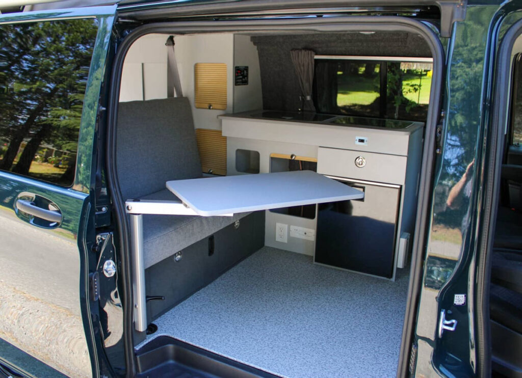 Interior of a Metris camper conversion with bench seat and table