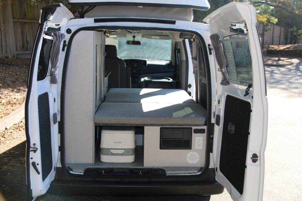 Rear door of NV200 camper opened to show a bed and portable toilet