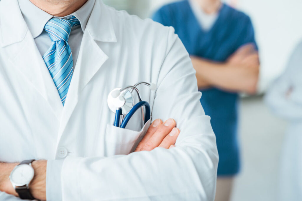 Professional medical team posing in a doctor's office, doctor's lab coat and stethoscope close up