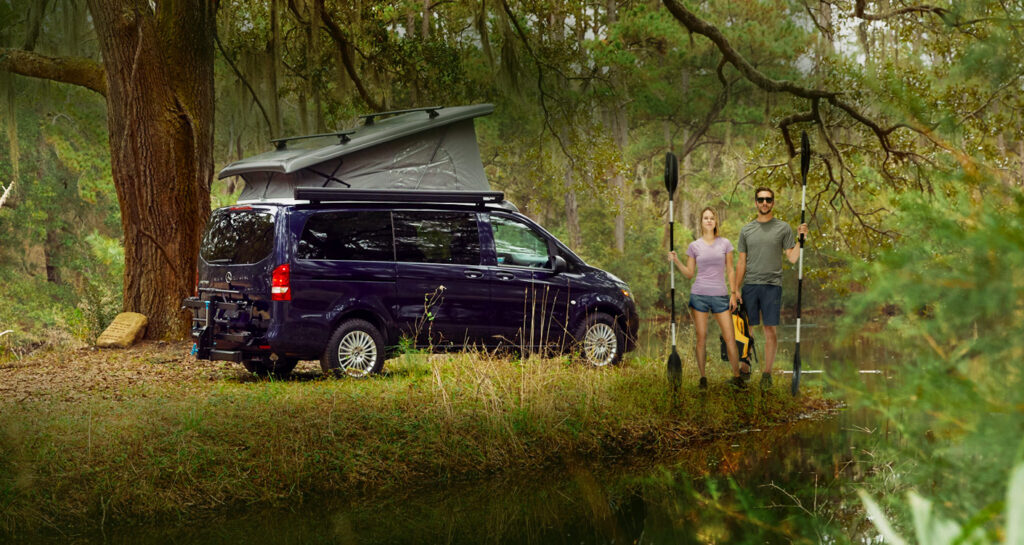 Couple standing by a Mercedes Metris camper in the woods