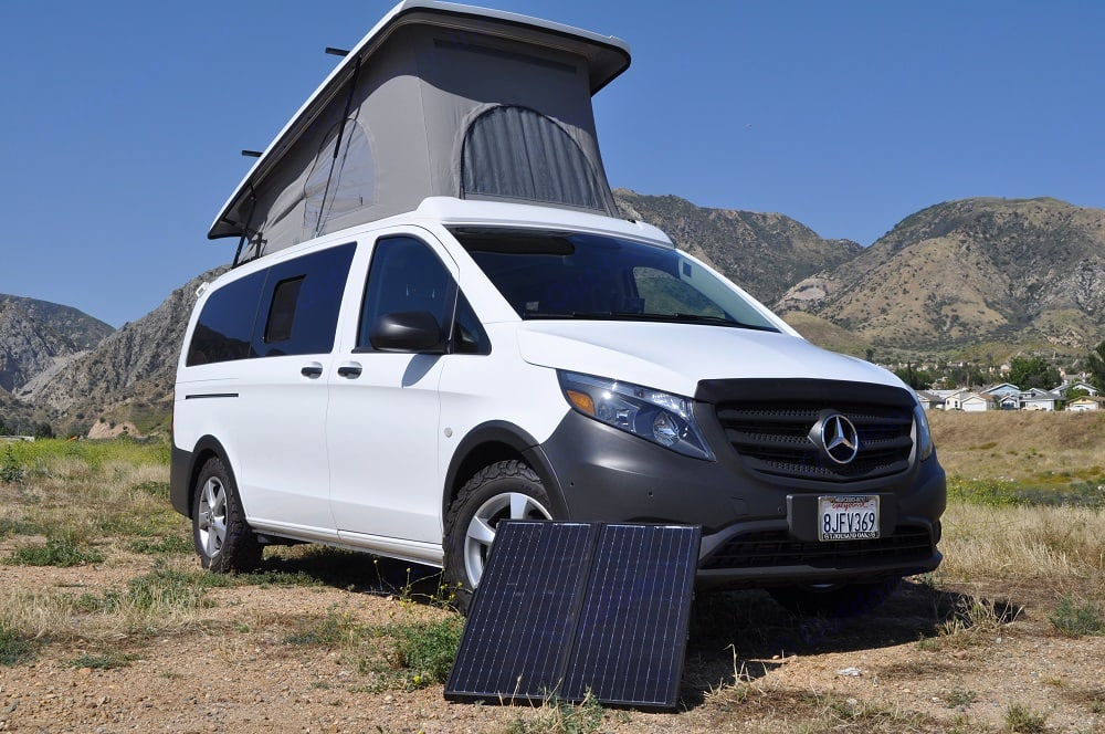 White Metris camper with pop top raised and a solar panel