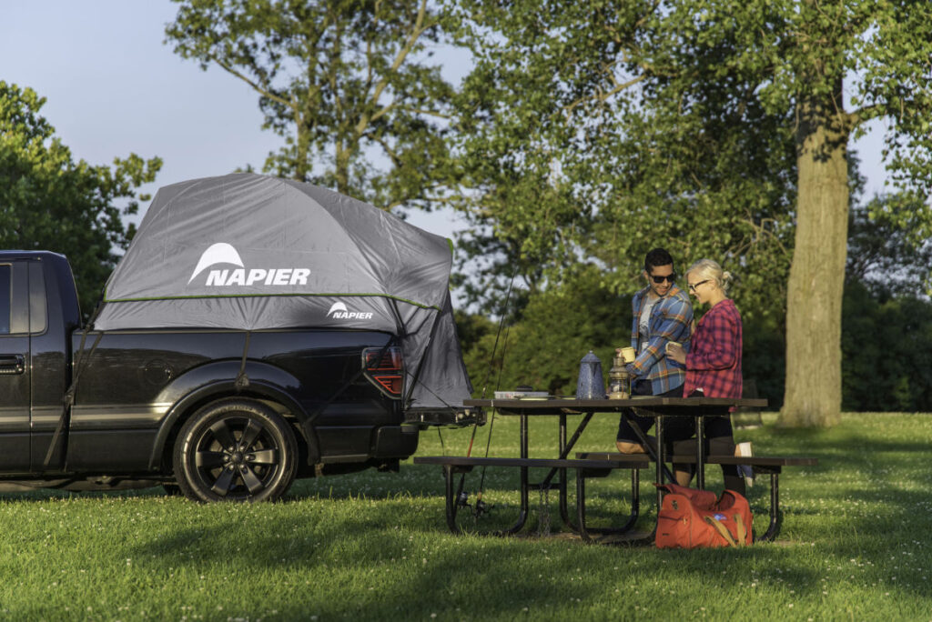 Two people at a picnic table and. atruck with a truck bed tent in the background