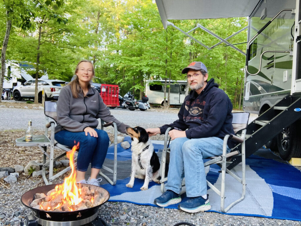 Couple sitting next to their dog and RV while RVing with dogs