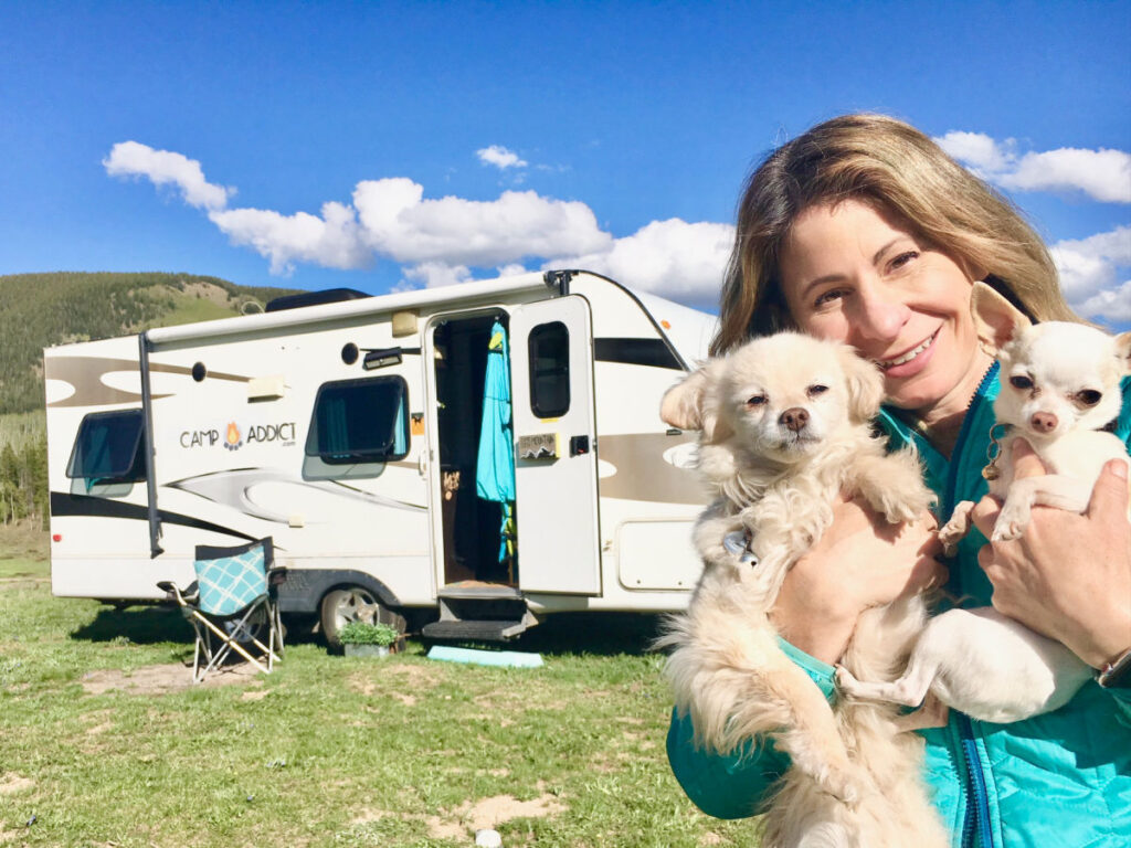 woman holding two small dogs in front of a camper while RVing with dogs