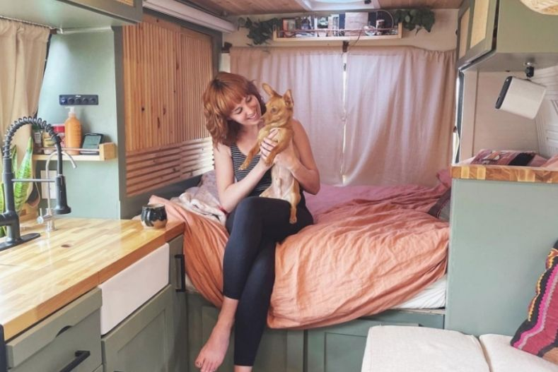 Savannah on bed in shuttle bus conversion, holding dog