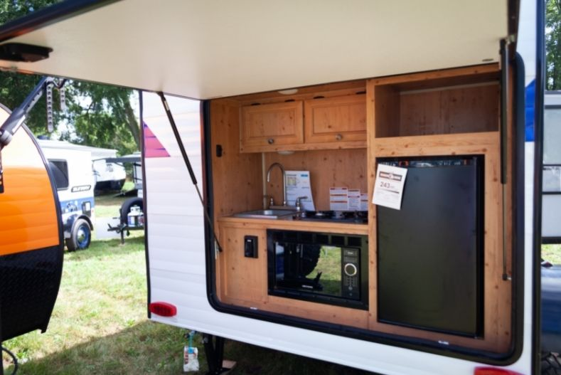 Sunray travel trailer exterior kitchen with wooden cabinets and black accessories