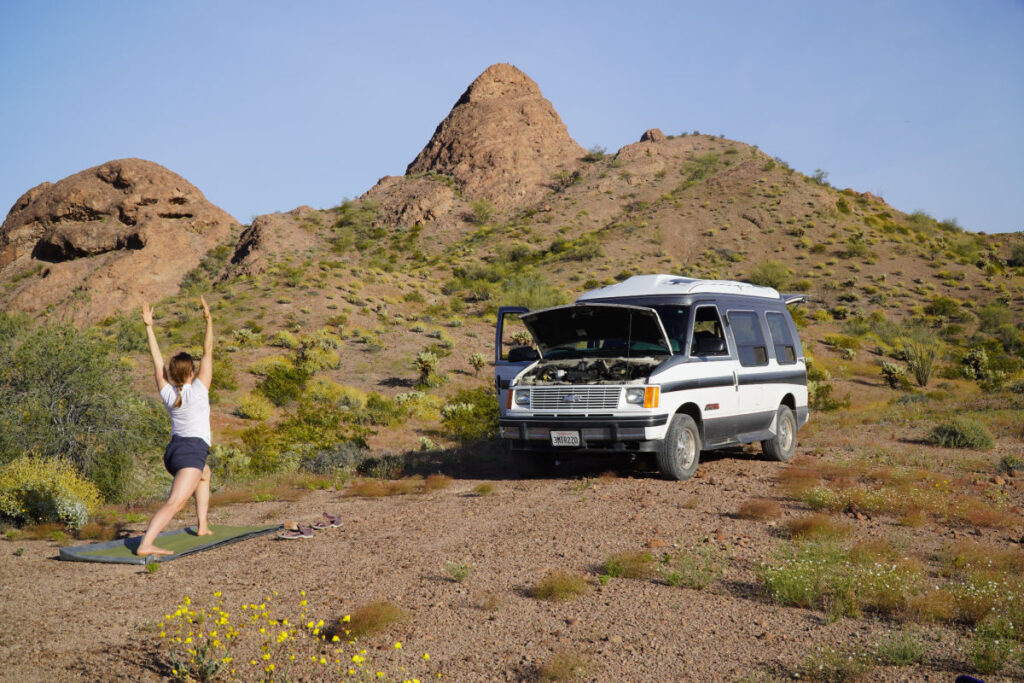 Woman doing yoga beside van