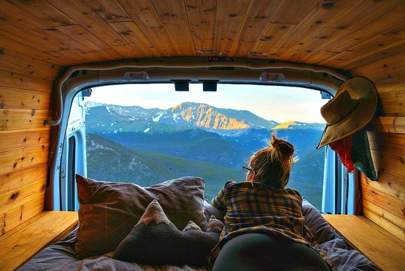 Woman looks out over mountains from campervan window