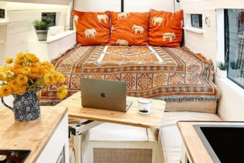 Van with white wood paneling, bohemian bedspread on bed, bench seating between bed and kitchen and slide-away table off to the side