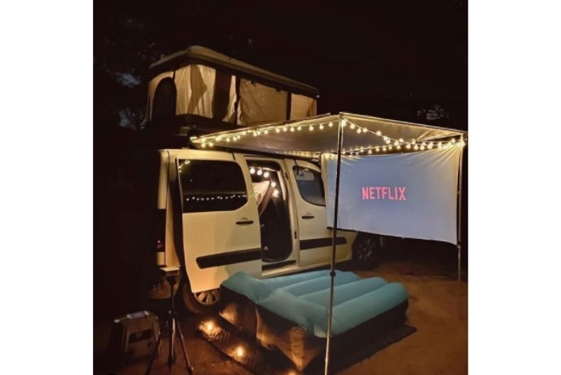 Projector screen hanging from awning outside van with air mattress set up to watch movie