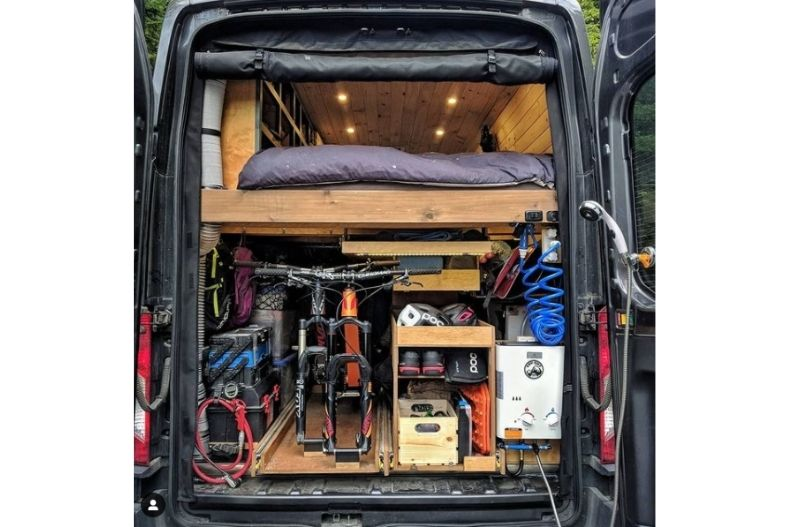 Camper van with lofted bed, storage below, and outdoor shower