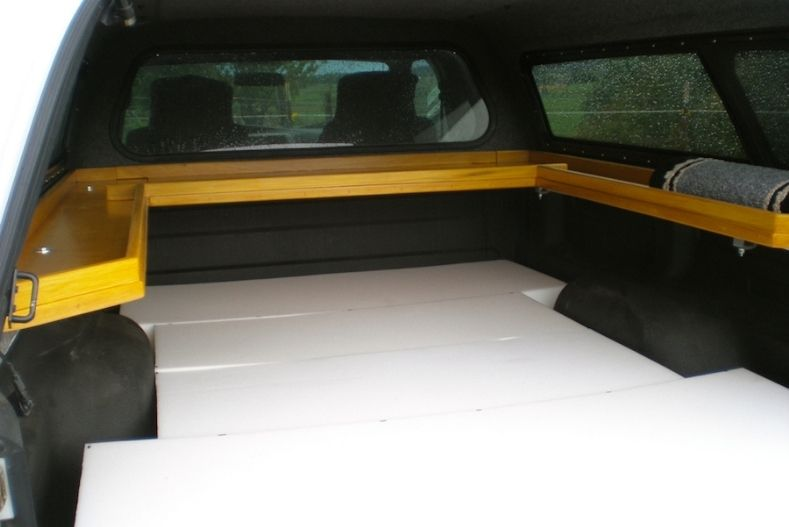 Floating shelves installed above foam sections used for bedding in a camper shell