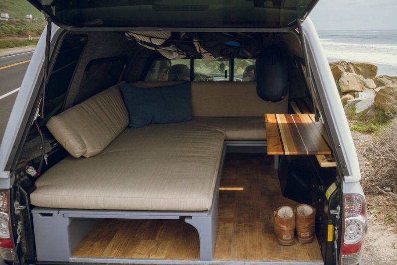 Wooden flooring and L shaped custom couch with desk platform in truck bed camper
