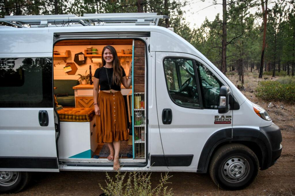 woman standing in the door of a campervan