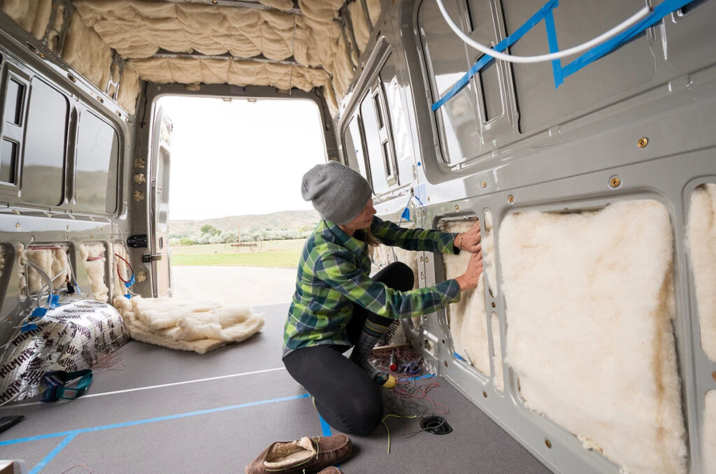 Woman putting wool insulation for a van in a panel van walls