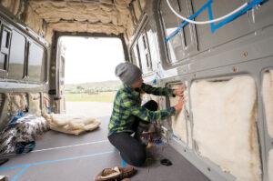 woman installing wool van insulation in a panel van