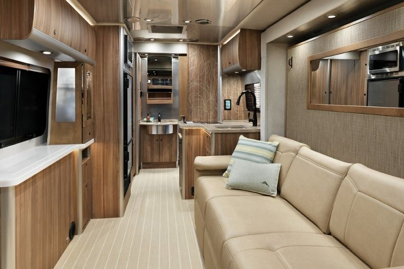 Airstream interior view with 3 cushion couch on left, facing cabinets and shelves, kitchenette in the background