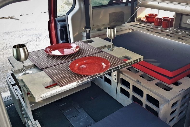 Minivan camper conversion kit with elements designed for multiple configurations. Table with bench seats and dish storage are displayed.
