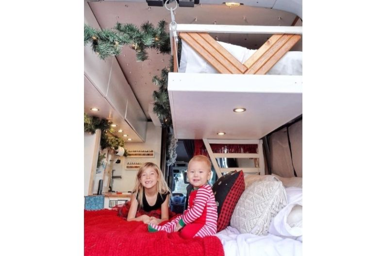 Two children sit on bed in camper van conversion, above them is a secured hanging platform bed