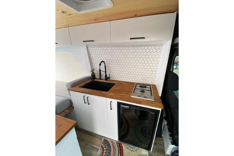 Camper van kitchen with white honeycomb backsplash, white cabinets, hardwood countertops and black fixtures.