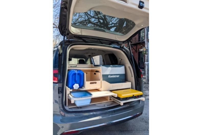 Rear hatch of van open to show minivan conversion kit with wooden drawers and shelves on sliders containing cooler, stove, water jug and collapsible container for washing