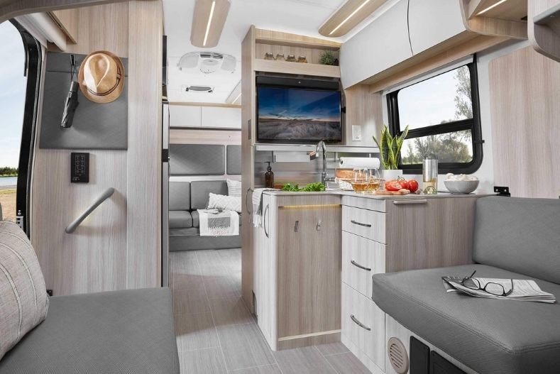 Leisure Travel Vans interior view with pale wood paneling and gray upholstery, kitchenette and bench seating are upfront with a sofa in back