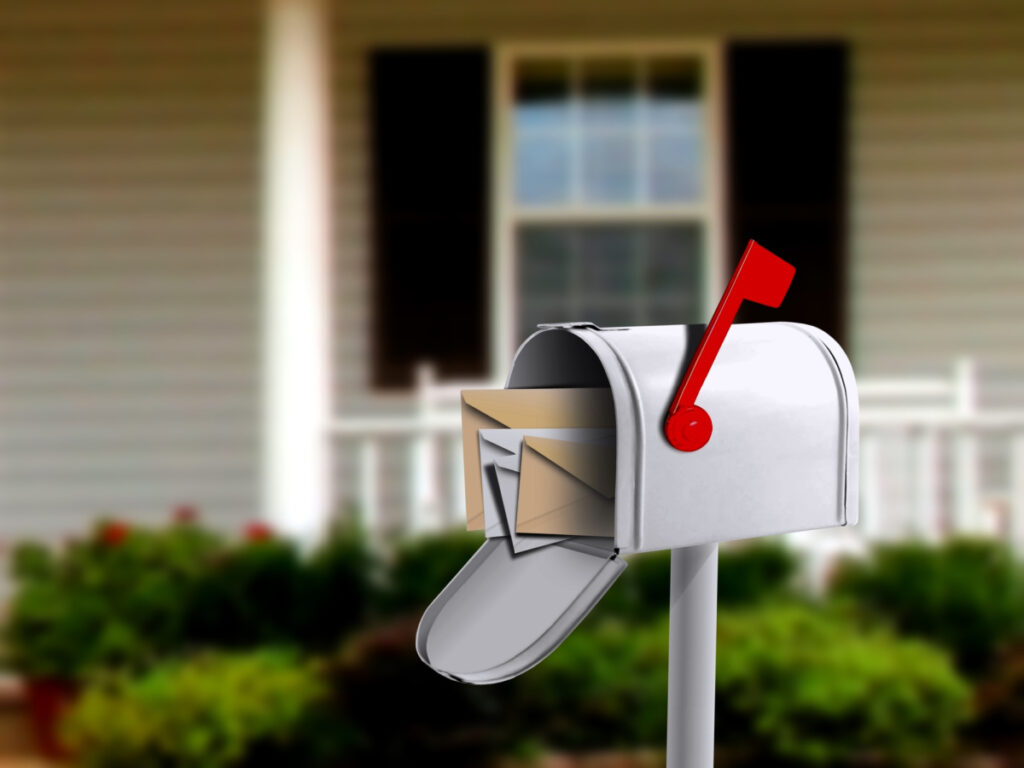 White mailbox in front of a house, another way to receive mail and packages on the road