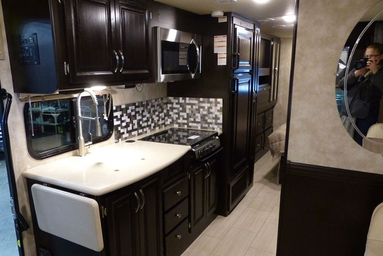 Nexus Viper Class B+ RV interior view with dark wood cabinets, kitchenette is shown with plenty of cabinet space