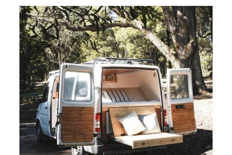 Van with back doors open and slide out cushioned outdoor seating