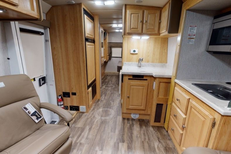 Phoenix Cruiser interior view with light natural wood looking cabinets in kitchenette, chair on opposite side and partial bedroom view in rear