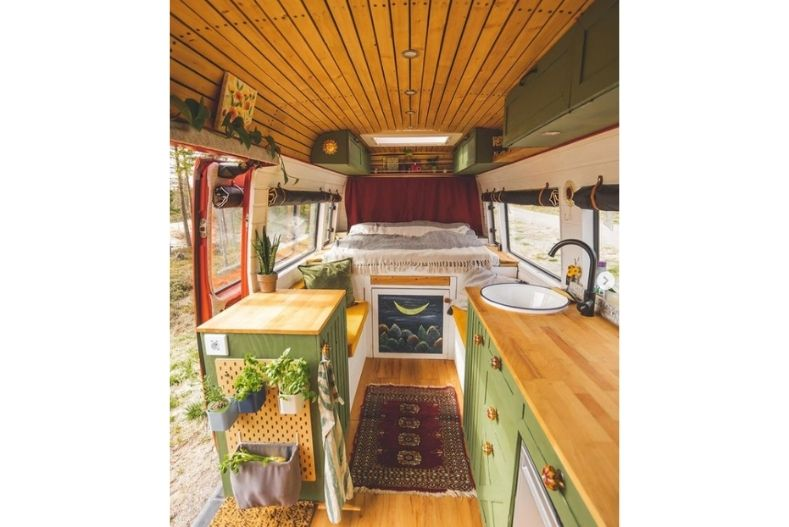 Campervan conversion interior with wood floor and ceiling, green cabinets and several hanging plants