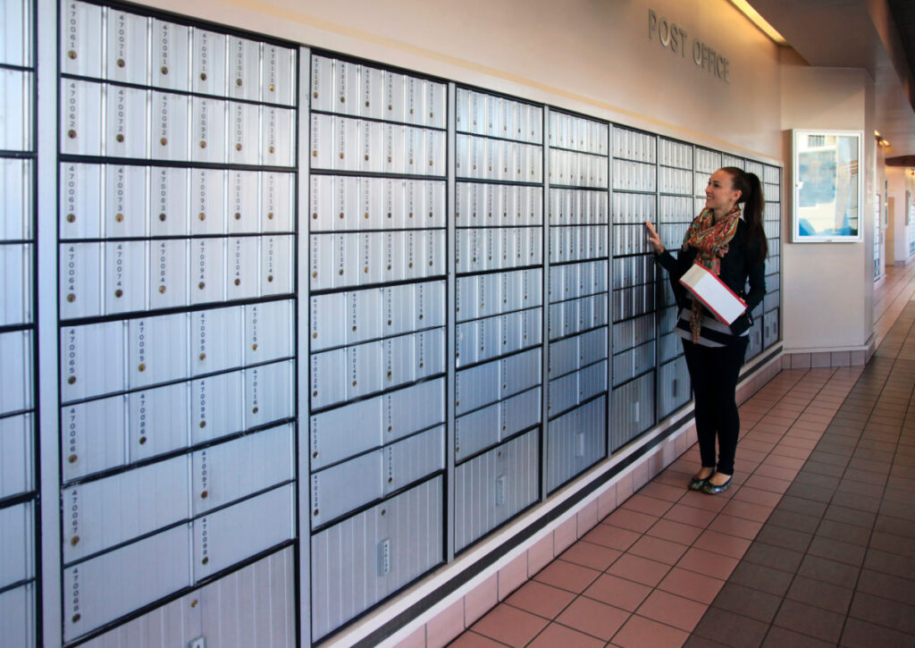 Woman inside a post office - general delivery is a way to get mail on the road