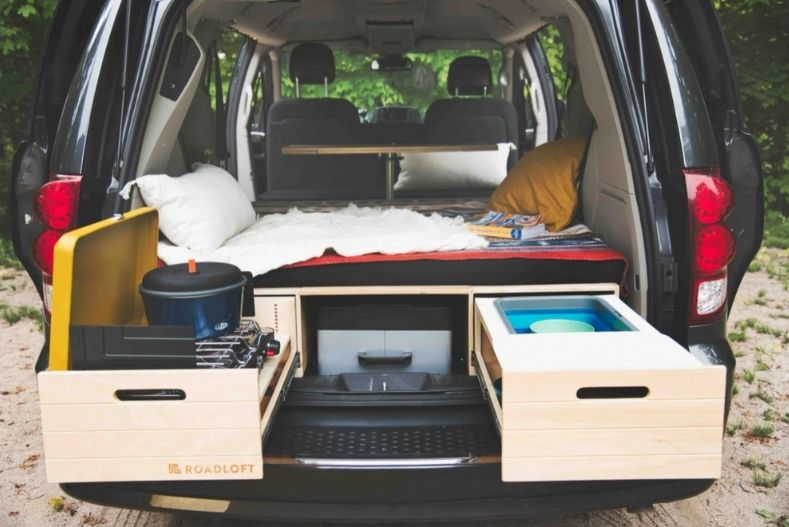 Roadloft's Dodge Grand Caravan conversion kit has platform bed with long drawer storage underneath and table in front