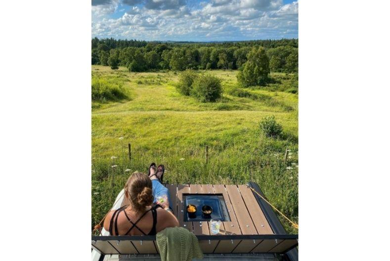 Woman sits on wooden campervan rooftop deck overlooking grassy fields
