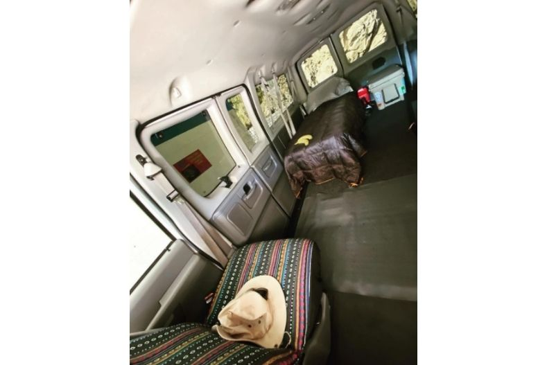 Simple van conversion idea with seats removed, camping cot and cooler